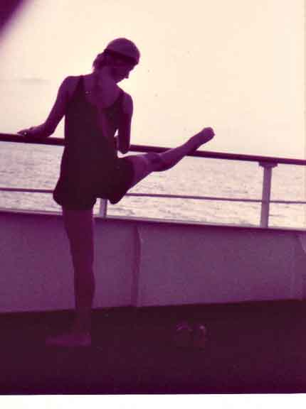 "ALT =[""Dr. Jolie Bookspan: Dr. Bookspan pioneered teaching fitness on cruise ships. Pictured here teaching the difference between a turned-out leg for art forms like dance, and the better healthier stretch of keeping the standing leg facing forward.]"